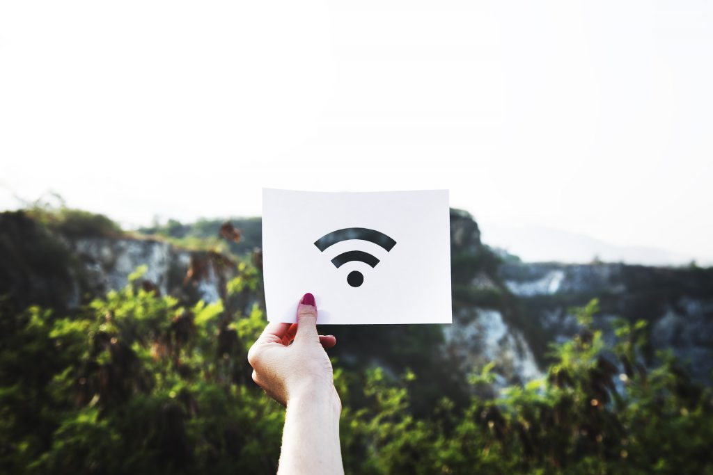 wifi signal image on paper held up in front of mountains in background